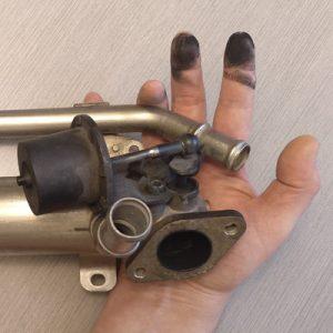 Una válvula EGR y una mano cubierta de carbonilla