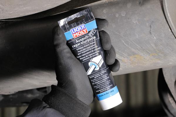 Mechaniker hält Auspuff-Reparaturpaste in der Hand