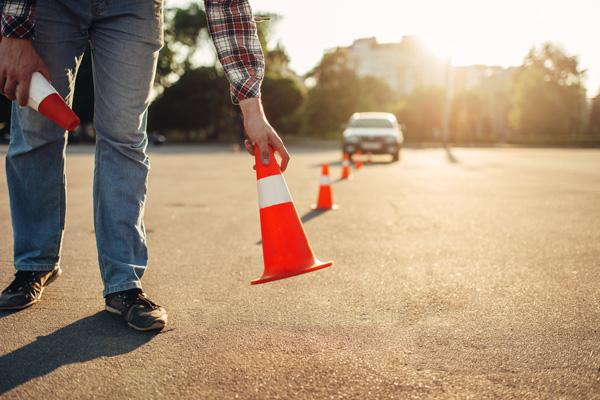 Mann stellt Leitkegel für einen Parcours beim Fahrsicherheitstraining für Senioren auf.