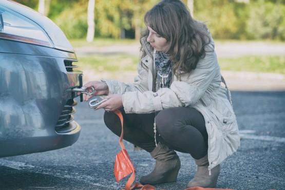 Frau befestigt Abschleppseil am Pannenfahrzeug