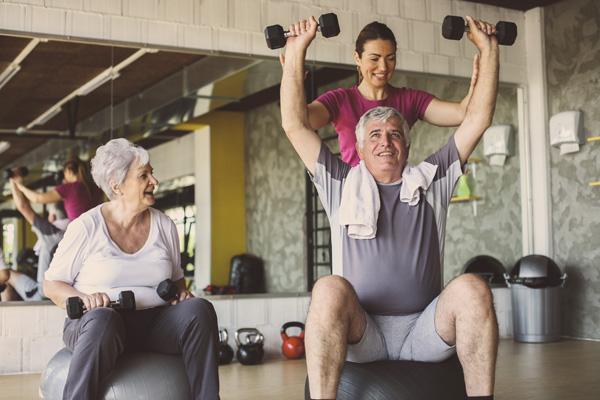 Trainerin unterstützt einen älteren Mann bei der richtigen Durchführung einer Sportübung.