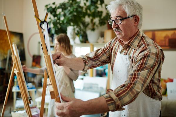 Älterer Herr nimmt an einem Kunstkurs teil.