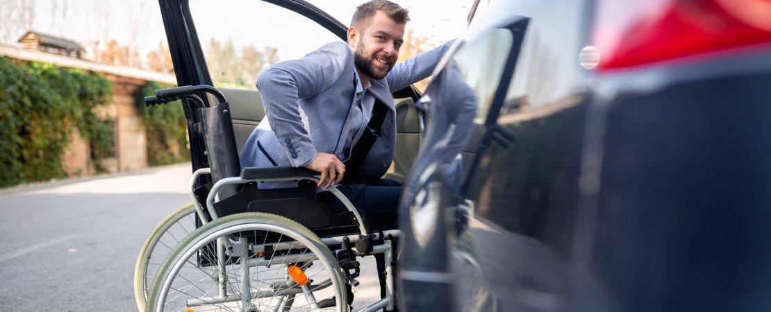 Rollstuhlfahrer steigt ins Auto ein