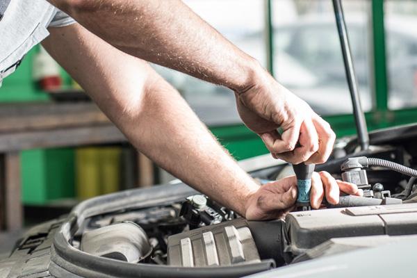 Automechaniker schraubt im Motorraum