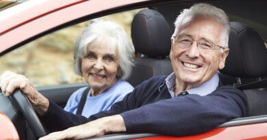 Älteres Paar sitzt im Auto und lächelt